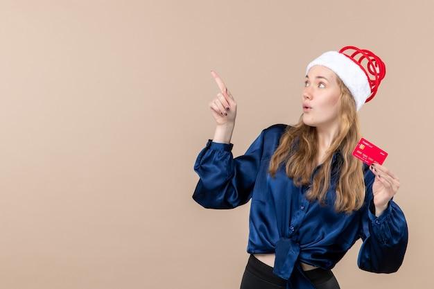 분홍색 배경 휴가 사진 새 해 크리스마스 돈 감정 여유 공간에 빨간 은행 카드를 들고 전면보기 젊은 여성 무료 사진