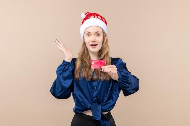 분홍색 배경 휴가 사진 새 해 크리스마스 돈 감정에 빨간 은행 카드를 들고 전면보기 젊은 여성 무료 사진