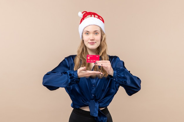 Front view young female holding red bank card on a pink background holiday photo new year emotion christmas money Free Photo