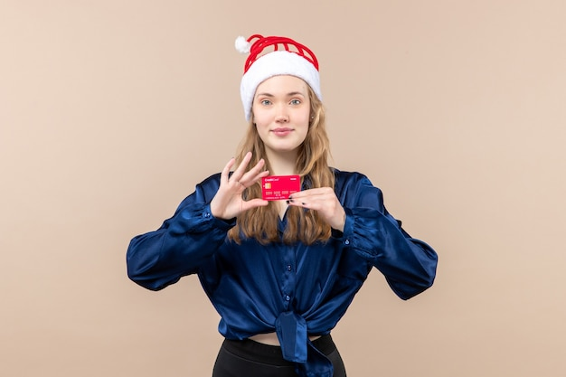 Front view young female holding red bank card on pink background holiday photo new year emotion christmas money Free Photo
