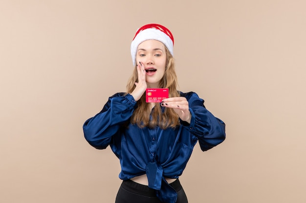 Front view young female holding red bank card on the pink background holiday photo new year emotion christmas money Free Photo