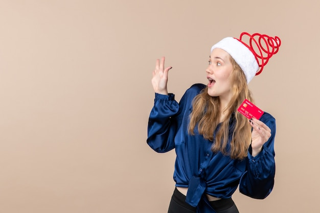 Front view young female holding red bank card on pink background holiday photo new year xmas money emotion free place Free Photo