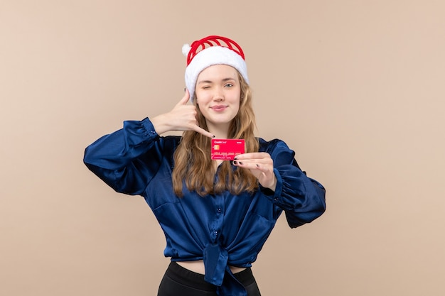 Front view young female holding red bank card on the pink background holiday photo new year xmas money emotion Free Photo