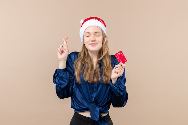 Front view young female holding red bank card on a pink background holiday xmas money photo new year emotion Free Photo