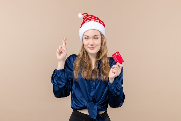 Front view young female holding red bank card on pink background holiday xmas money photo new year emotion Free Photo