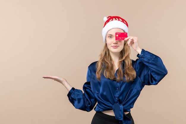 Front view young female holding red bank card on pink background holiday xmas money photo new year emotions Free Photo