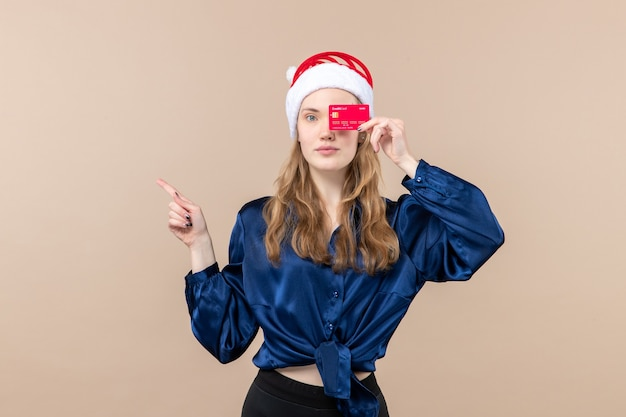 Front view young female holding red bank card on pink background holiday xmas money photos new year emotion Free Photo