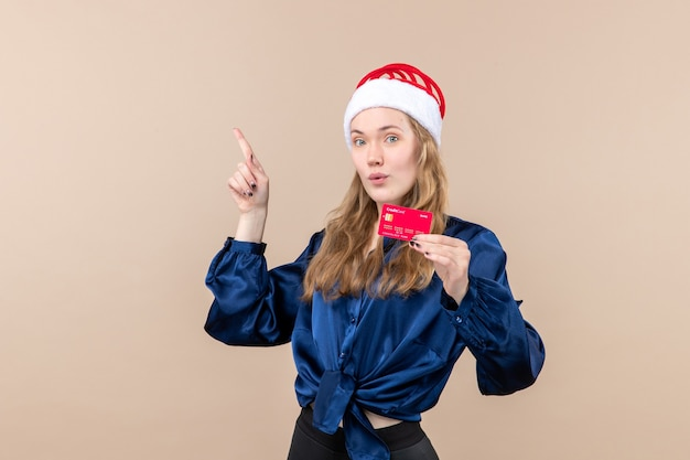 Front view young female holding red bank card on pink background holidays photo new year xmas money emotion Free Photo