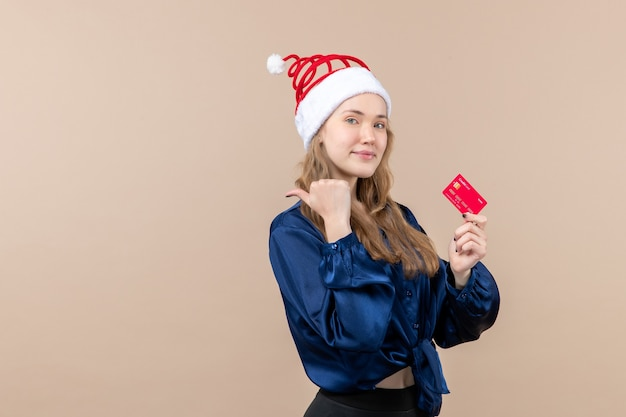 Front view young female holding red bank card on pink background money holiday new year xmas photo emotion free place Free Photo