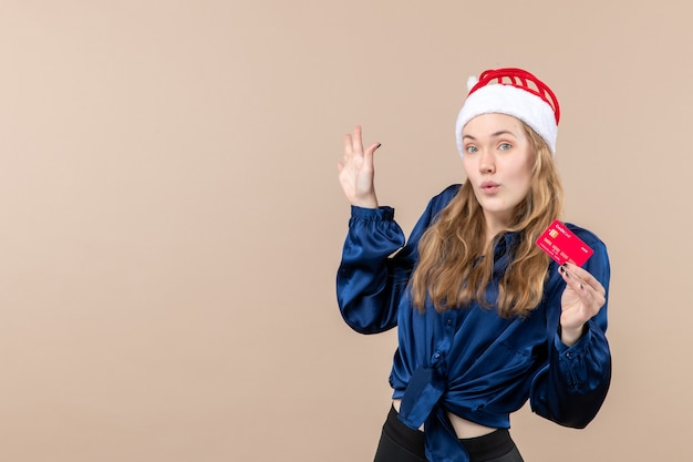 Front view young female holding red bank card on pink background money holiday photo new year xmas emotion Free Photo