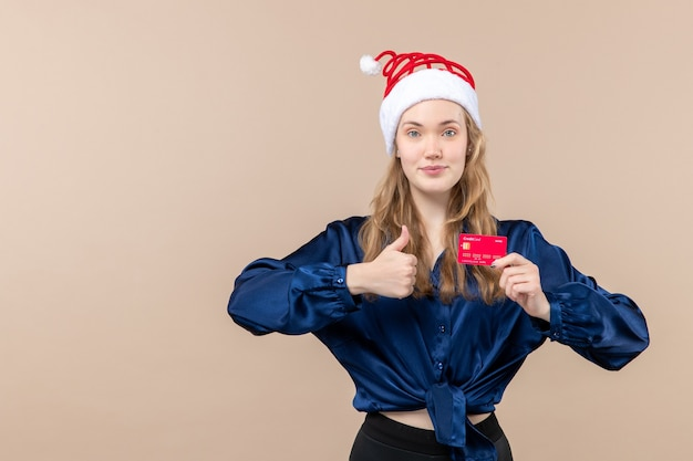 Front view young female holding red bank card on pink background money holidays photo new year xmas emotion free place Free Photo