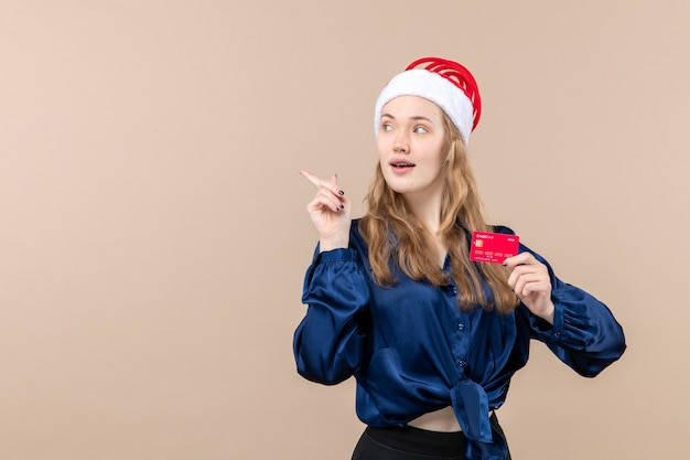 Front view young female holding red bank card on pink background money holidays photo new year xmas emotions free place Free Photo