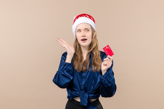 Front view young female holding red bank card on a pink background money photo holiday new year xmas emotion Free Photo