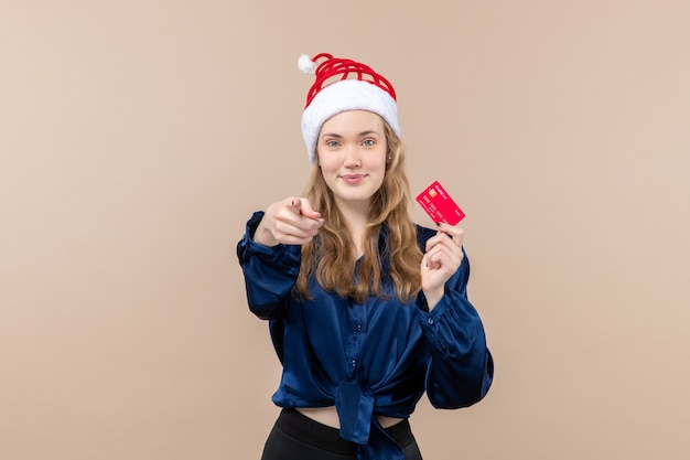 Front view young female holding red bank card on pink background money photo holiday new year xmas emotion Free Photo