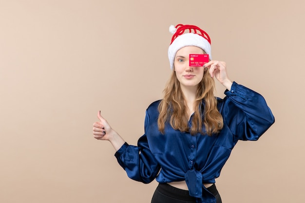 Front view young female holding red bank card on pink background new year holiday xmas photo emotion money Free Photo