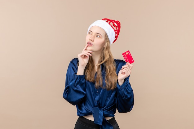 Front view young female holding red bank card on a pink background xmas money photo holiday new year emotion Free Photo