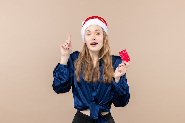 Front view young female holding red bank card on the pink background xmas money photo holiday new year emotion Free Photo