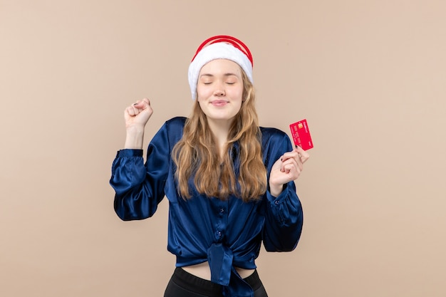 Front view young female holding red bank card on pink background xmas money photo holiday new year emotions Free Photo