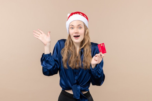 Front view young female holding red bank card on pink background xmas money photo holidays new year emotion Free Photo