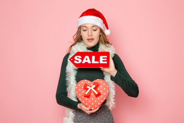 正面図赤いセールを保持している若い女性がピンクの壁に書き込みとプレゼントクリスマス新年ファッション感情休日 無料写真