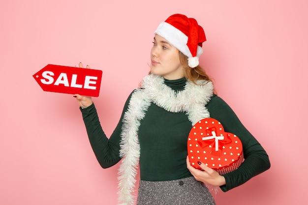 正面図赤いセールを保持している若い女性がピンクの壁に書き込みとプレゼントクリスマス新年ショッピング感情休日の色 無料写真