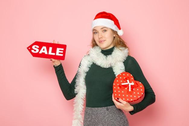 빨간색 판매 쓰기와 핑크 벽 크리스마스 새 해 쇼핑 감정 휴일 색상에 선물을 들고 전면보기 젊은 여성 무료 사진