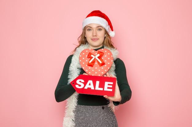 赤いセールを保持し、ピンクの壁にプレゼントクリスマス新年ショッピング感情休日 無料写真