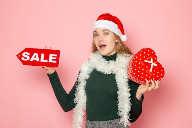 赤いセールの執筆を保持し、ピンクの壁にプレゼントクリスマス新年ショッピング感情休日の正面図若い女性 無料写真