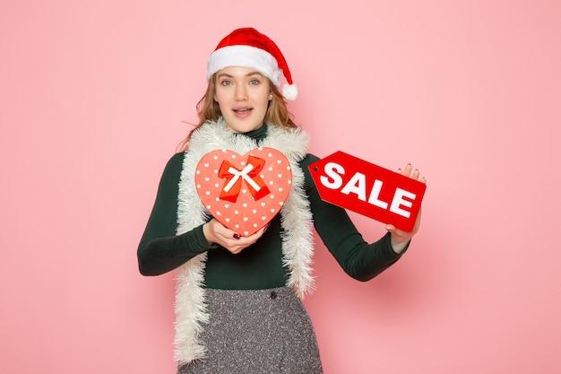 正面図赤いセールを保持している若い女性がピンクの壁に書き込みとプレゼントクリスマス新年ショッピングファッション感情休日 無料写真