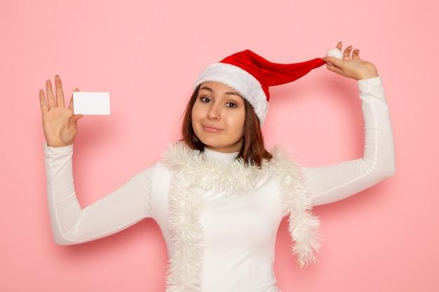 핑크 벽 크리스마스 휴일 새 해 패션 색상 돈에 흰색 은행 카드를 들고 전면보기 젊은 여성 무료 사진