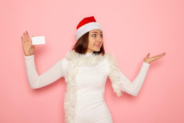 분홍색 벽 크리스마스 새 해 색상 돈 휴가에 흰색 은행 카드를 들고 전면보기 젊은 여성 무료 사진