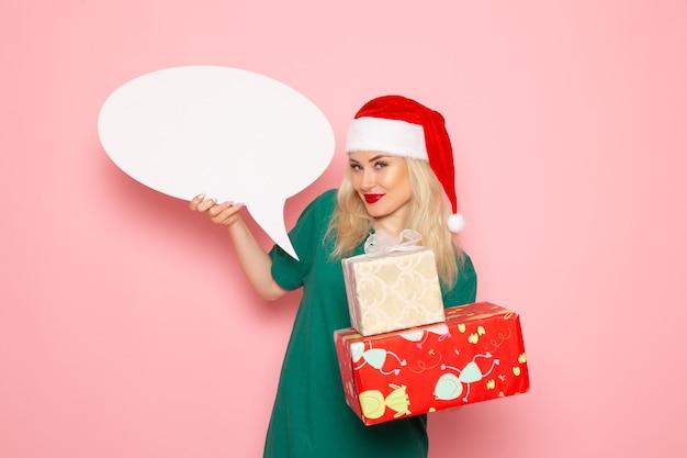 Вид спереди молодая женщина держит рождественские подарки и белый знак на розовой стене женщина подарок цвет снега фото новогодние праздники Бесплатные Фотографии