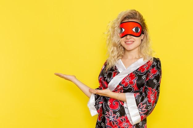 밤 가운에 전면보기 젊은 여성과 노란색 벽에 웃는 잠을 준비하는 아이 마스크 착용 밤 수면 여성 어둠 색상 무료 사진