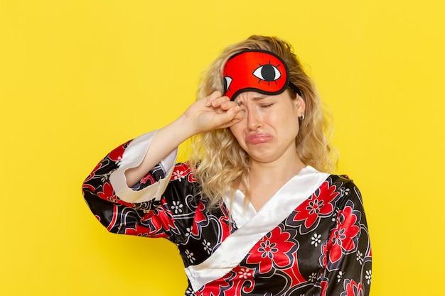 夜のローブで若い女性の正面図と明るい黄色の壁で偽の泣きを眠る準備をしているアイマスクを身に着けている女性モデルの夜のベッド 無料写真