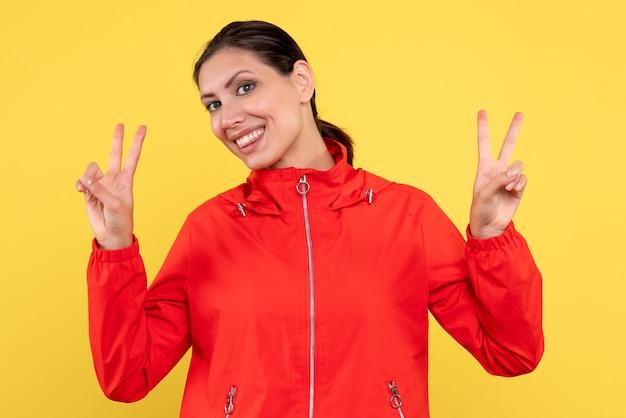 Вид спереди молодая женщина в красном пальто на желтом фоне Бесплатные Фотографии