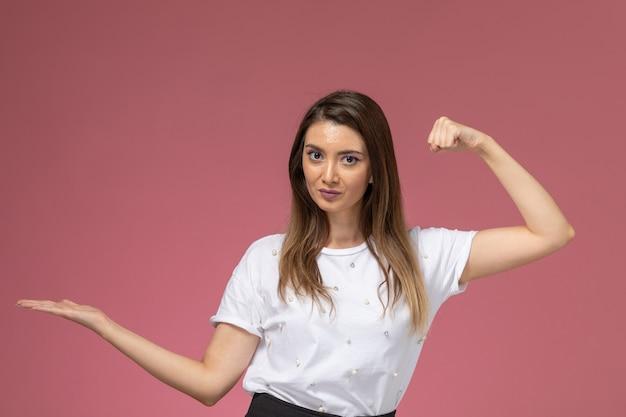 제기 손으로 포즈와 분홍색 벽에 Flexing 흰 셔츠에 전면보기 젊은 여성, 컬러 여자 모델 포즈 여자 무료 사진