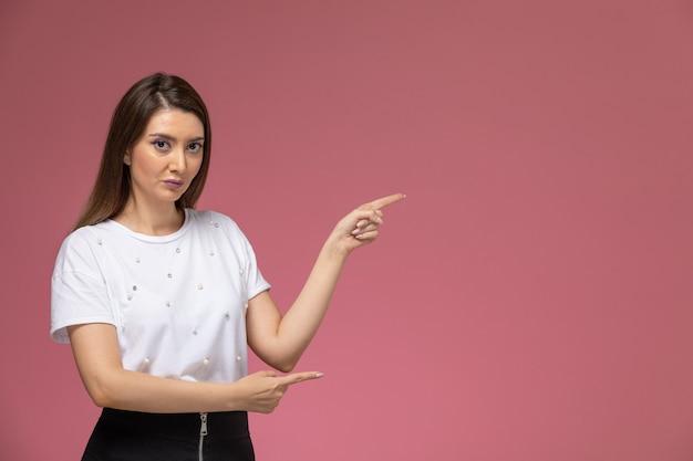 ピンクの壁に上げられた手でポーズをとる白いシャツの正面図若い女性、カラー女性モデルポーズの女性 無料写真
