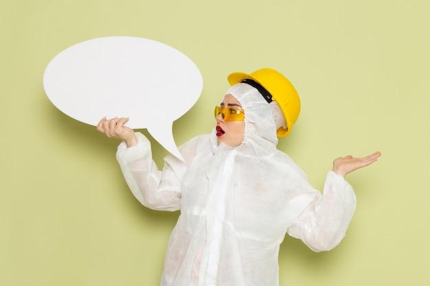 Вид спереди молодая женщина в белом специальном костюме и желтом шлеме держит большой белый знак на зеленых космических костюмах химии Бесплатные Фотографии