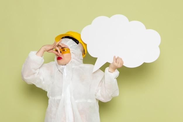 Вид спереди молодая женщина в белом специальном костюме и желтом шлеме с белым знаком, закрывающим нос на зеленом пространстве, химическая работа Бесплатные Фотографии