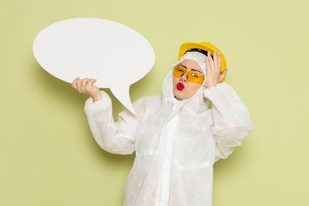 Молодая женщина в белом специальном костюме и желтом шлеме, держащая белый знак с легкой улыбкой на зеленом пространстве, работает по химии Бесплатные Фотографии