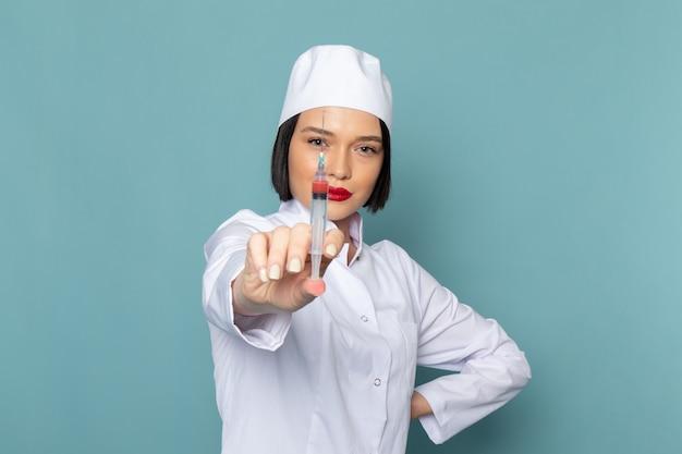 Una giovane infermiera femminile di vista frontale nell'iniezione medica bianca della tenuta del vestito sul medico dell'ospedale della medicina dello scrittorio blu Foto Gratuite