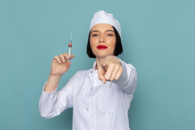 A front view young female nurse in white medical suit holding injection on the blue desk medicine hospital doctor Free Photo