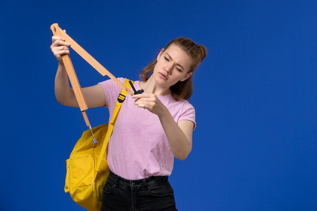 Front view of young female in pink t-shirt wearing yellow backpack holding wooden figure on blue wall Free Photo