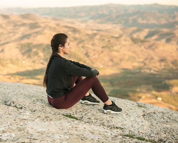 Front view young female sitting on top of mountain Free Photo