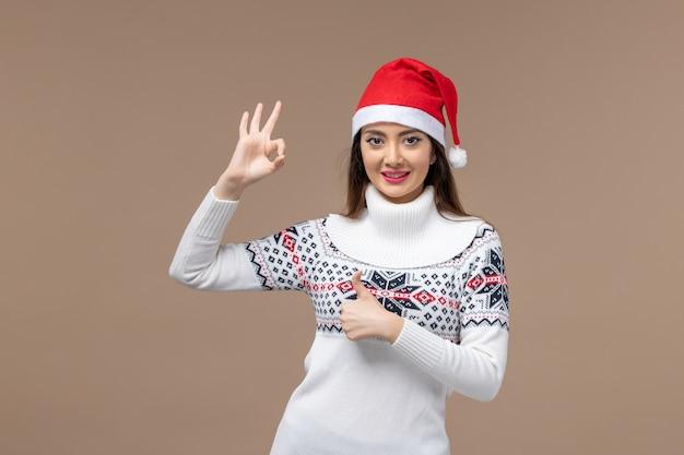 Vista frontale giovane donna sorridente con tappo rosso su sfondo marrone emozione natale capodanno Foto Gratuite