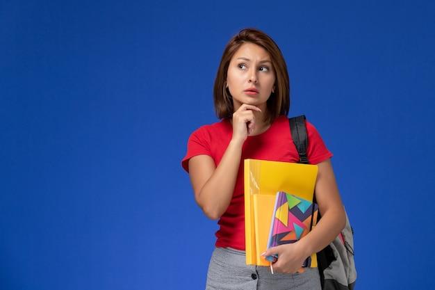 파란색 배경에 파일 및 카피 북 생각 들고 배낭을 입고 빨간 셔츠에 전면보기 젊은 여성 학생. 무료 사진