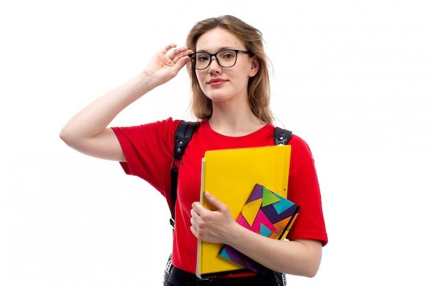 Una giovane studentessa di vista frontale negli archivi rossi dei quaderni della tenuta della borsa del nero della camicia che sorride sul bianco Foto Gratuite