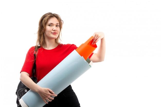 Una giovane studentessa di vista frontale nella borsa rossa del nero della camicia che sorride tenendo grande archivio sul bianco Foto Gratuite
