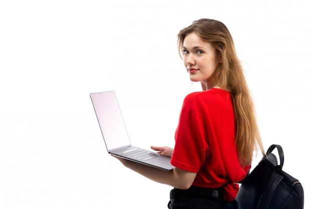 A front view young female student in red shirt black bag using laptop on the white Free Photo