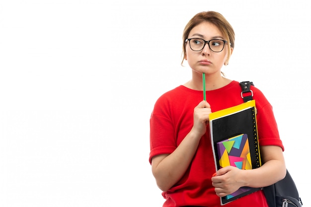 A front view young female student in red t-shirt black jeans holding different copybooks and files holding pencil thinking on the white Free Photo